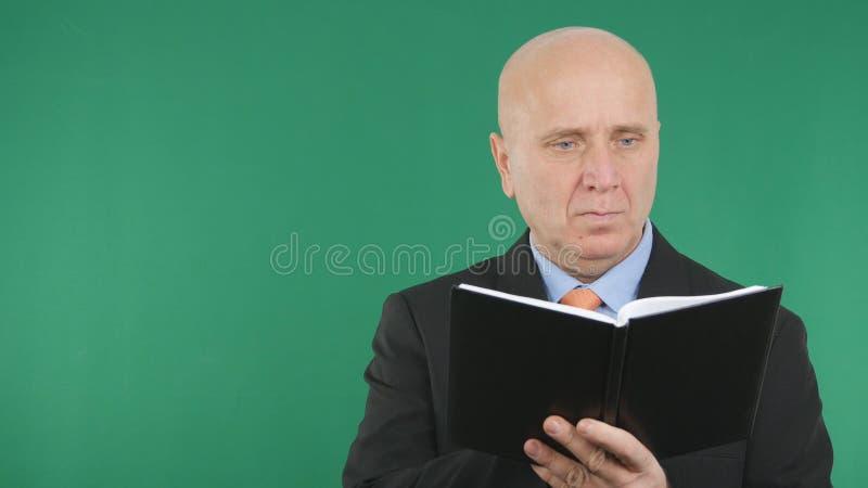 Homme d'affaires sûr Use Agenda pour prendre des notes photo libre de droits