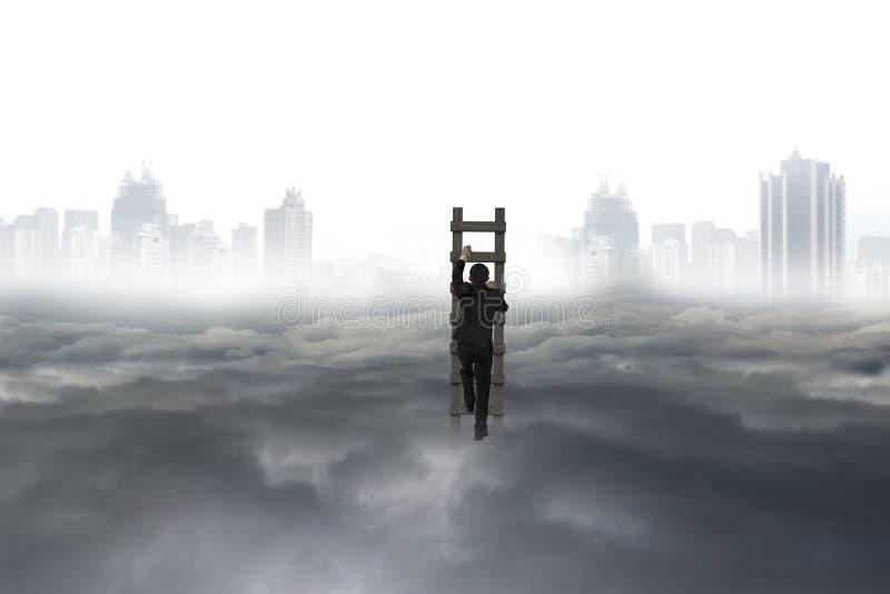 Homme d'affaires s'élevant sur l'échelle en bois avec le nuage de paysage de ville photos libres de droits