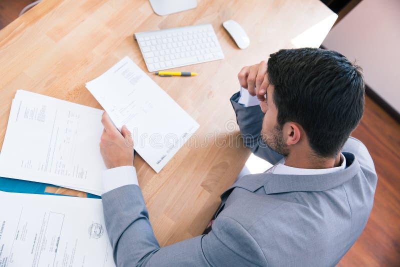 Homme d'affaires s'asseyant à la table avec des documents photos stock