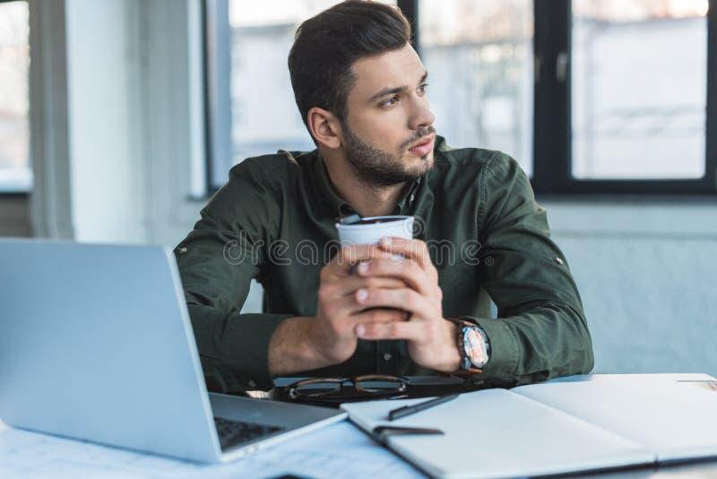 homme d'affaires s'asseyant à la table dans le bureau et tenant la tasse photo libre de droits