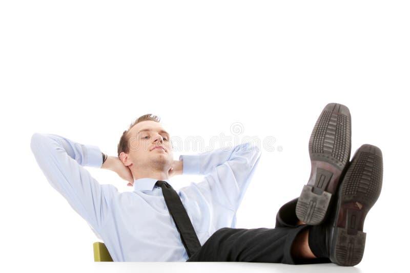 Homme d'affaires s'asseyant au bureau image stock