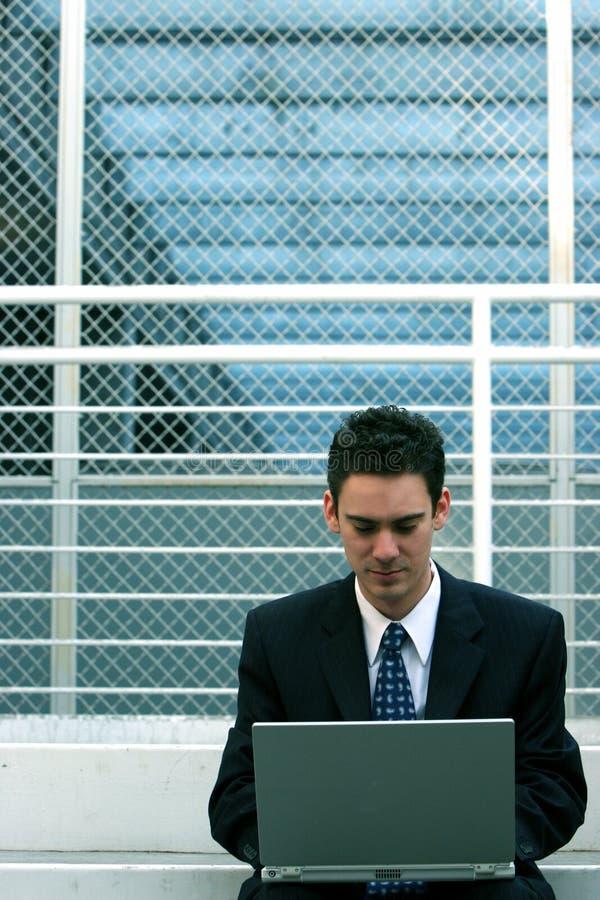 Homme d'affaires s'asseyant avec l'ordinateur portatif photo libre de droits