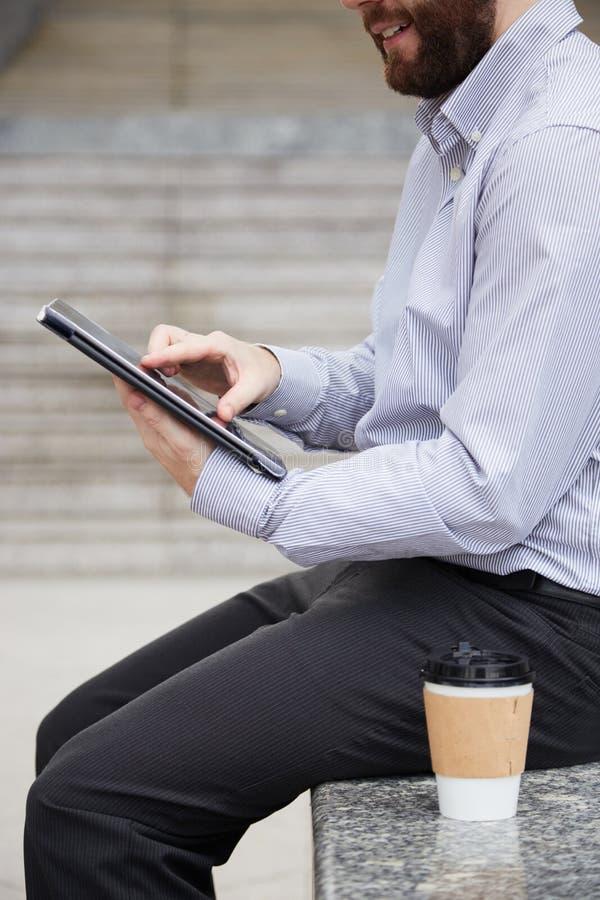 Homme d'affaires s'asseyant avec le comprimé numérique dehors images libres de droits
