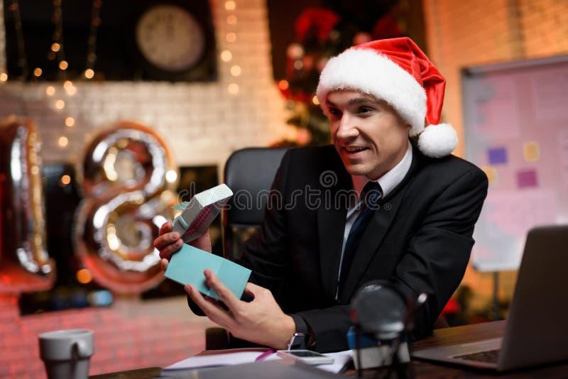 Homme d'affaires s'asseyant dans le bureau et travaillant au ` s Ève de nouvelle année Il considère avec enthousiasme le cadeau d photographie stock libre de droits