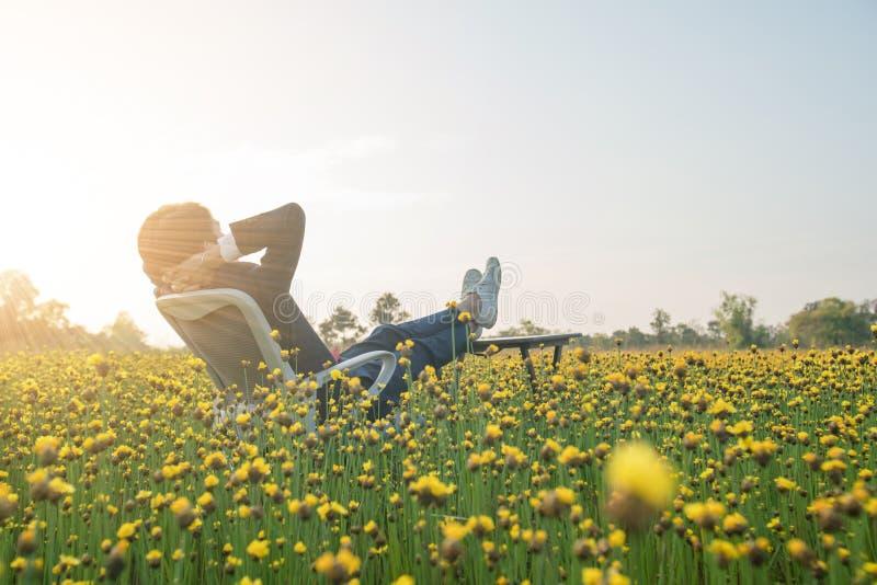 Homme d'affaires s'asseyant dans le fauteuil de bureau et détendant dans f jaune photographie stock libre de droits