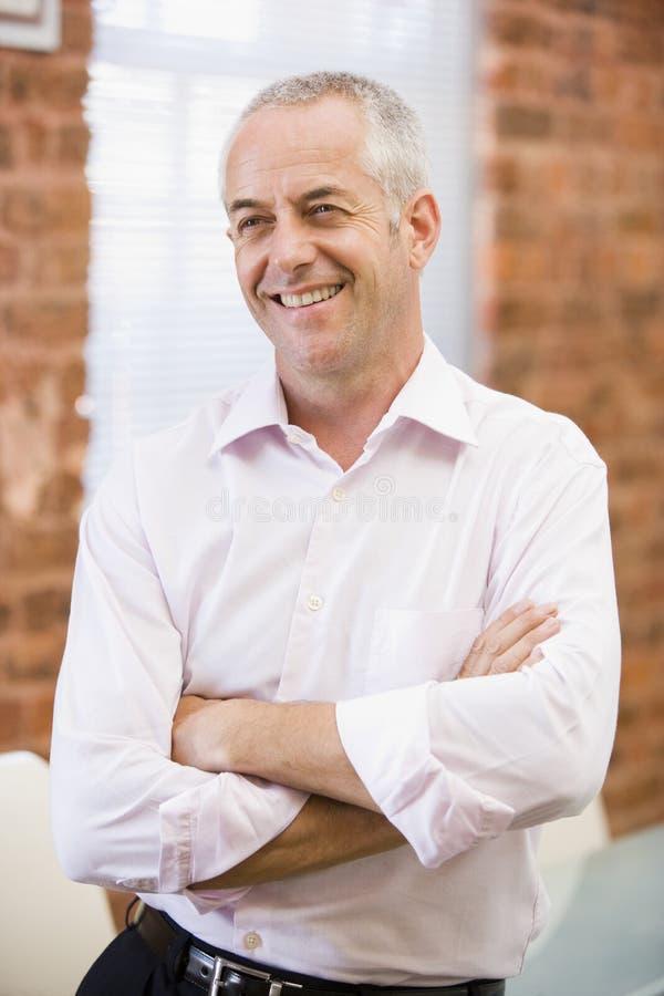 Homme d'affaires s'asseyant dans le sourire de bureaux image stock