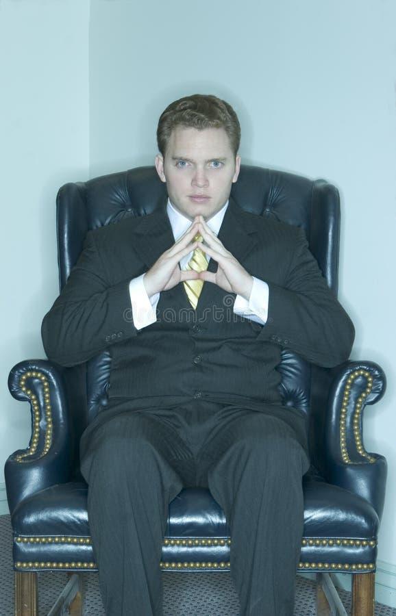 Homme d'affaires s'asseyant dans sa présidence image stock