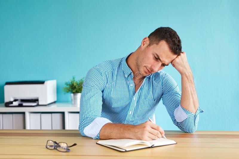 Homme d'affaires s'asseyant dans son bureau et écrivant le plan photos libres de droits