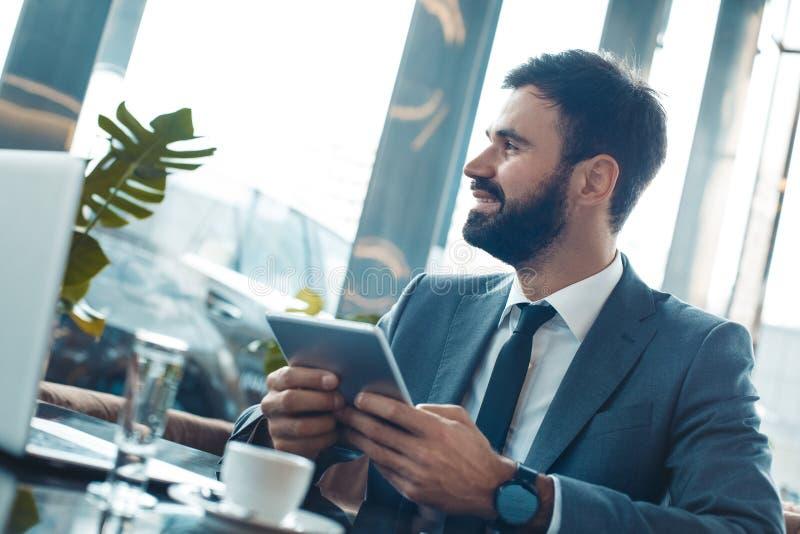 Homme d'affaires s'asseyant dans un restaurant de centre d'affaires tenant le comprimé numérique regardant la fenêtre images stock