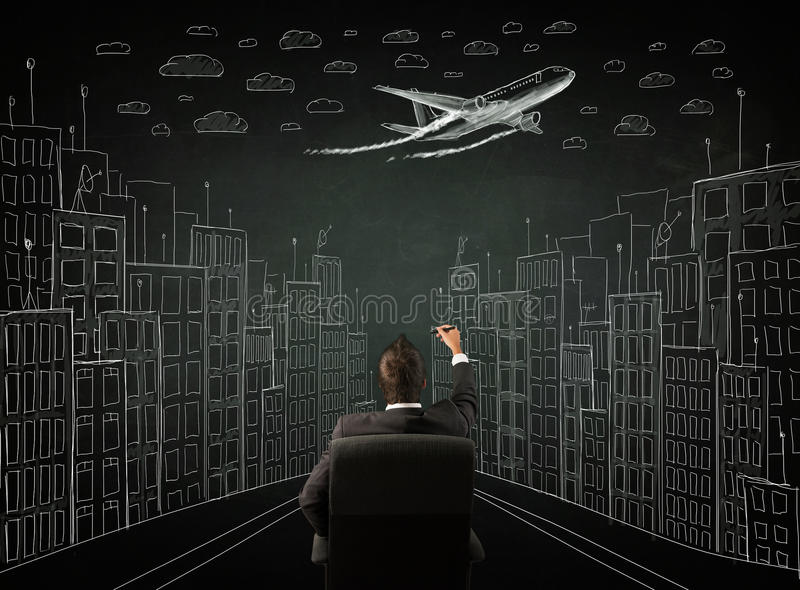 Homme d'affaires s'asseyant devant un dessin de paysage urbain sur un chalkbo photos stock