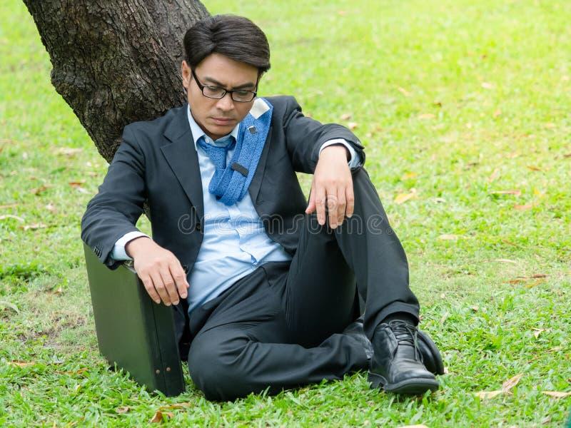 Homme d'affaires s'asseyant en parc d'extérieur et soumis à une contrainte en raison de l'échec de travail d'affaires image stock