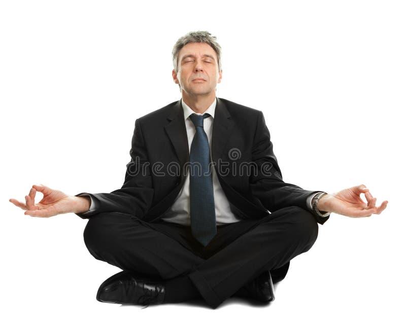 Homme d'affaires s'asseyant en position de yoga images stock