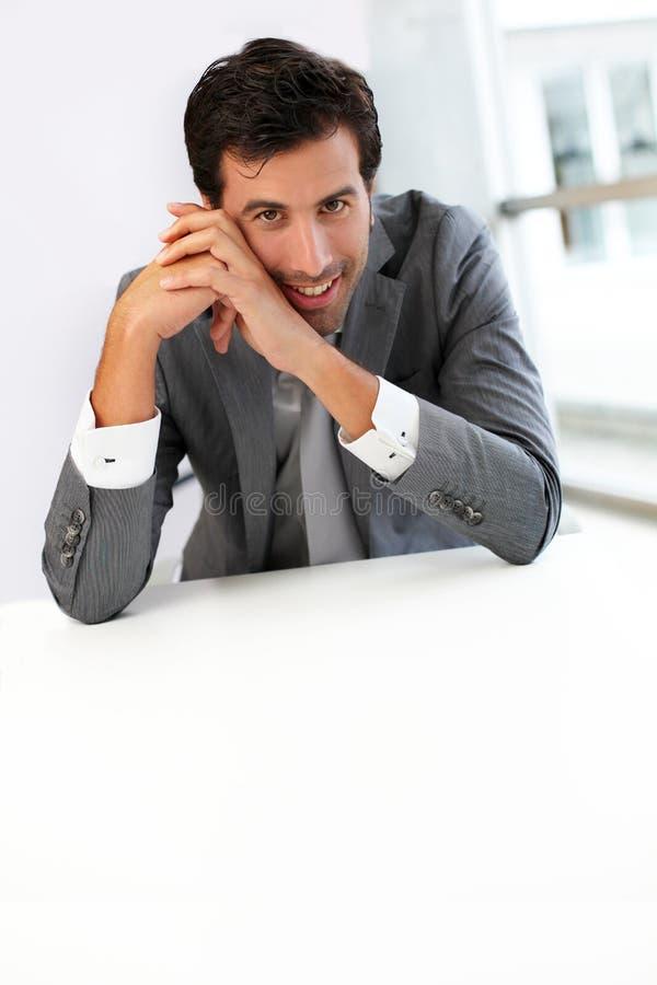 Homme d'affaires s'asseyant par le bureau images libres de droits