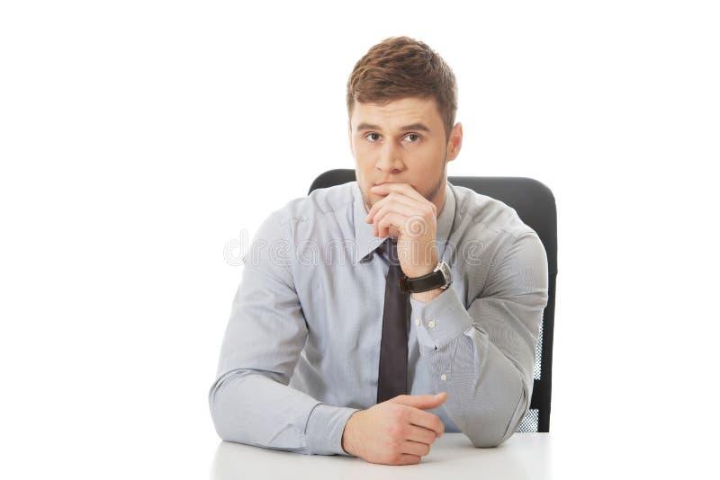 Homme d'affaires s'asseyant par un bureau dans le bureau images libres de droits
