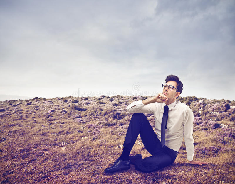 Homme d'affaires s'asseyant sur l'herbe photographie stock