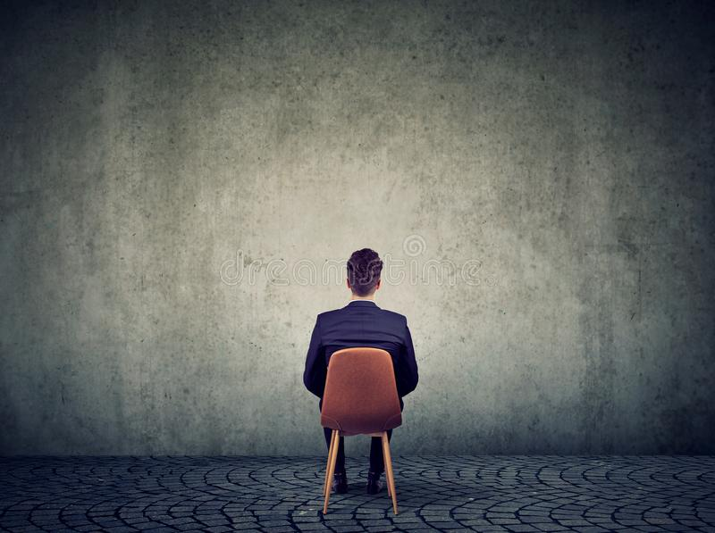 Homme d'affaires s'asseyant sur la chaise devant le mur en béton résolvant un problème photographie stock