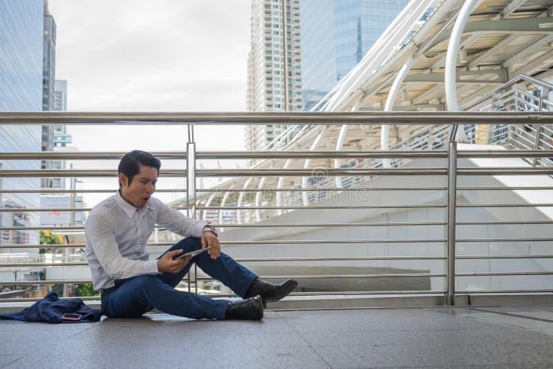 Homme d'affaires s'asseyant sur la rue et le comprimé d'utilisation pour la découverte un nouveau travail, concept de problème de image stock