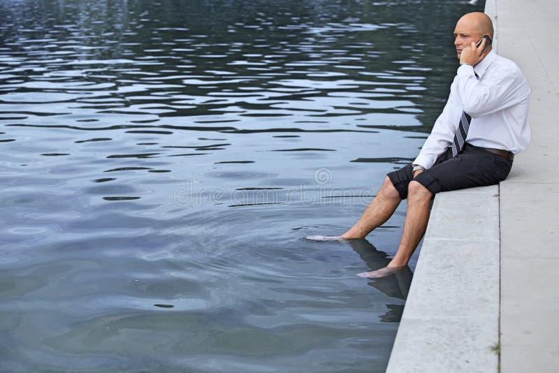 Homme d'affaires s'asseyant sur le mur par le lac, utilisant le téléphone portable images libres de droits