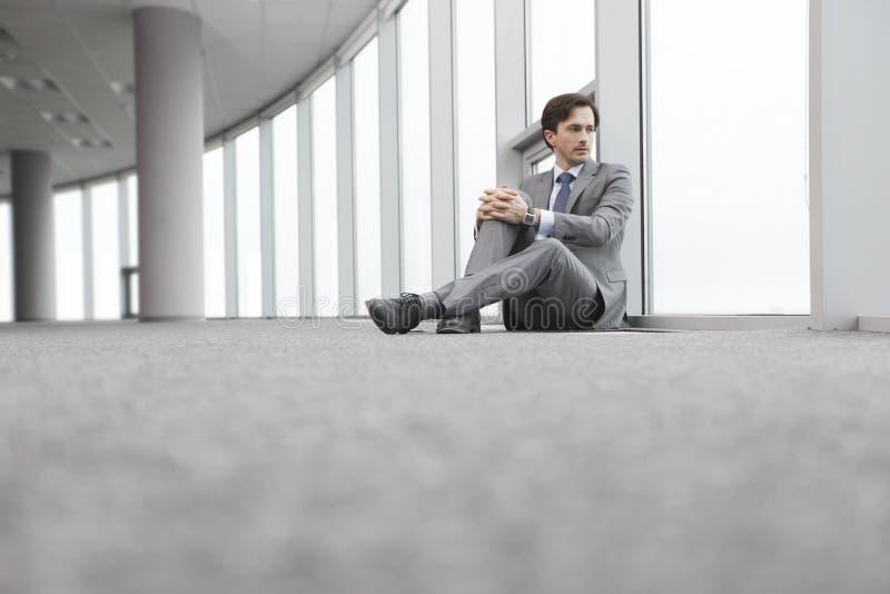 Homme d'affaires s'asseyant sur le plancher image stock