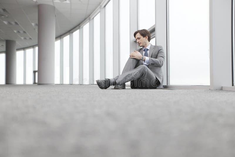 Homme d'affaires s'asseyant sur le plancher images stock