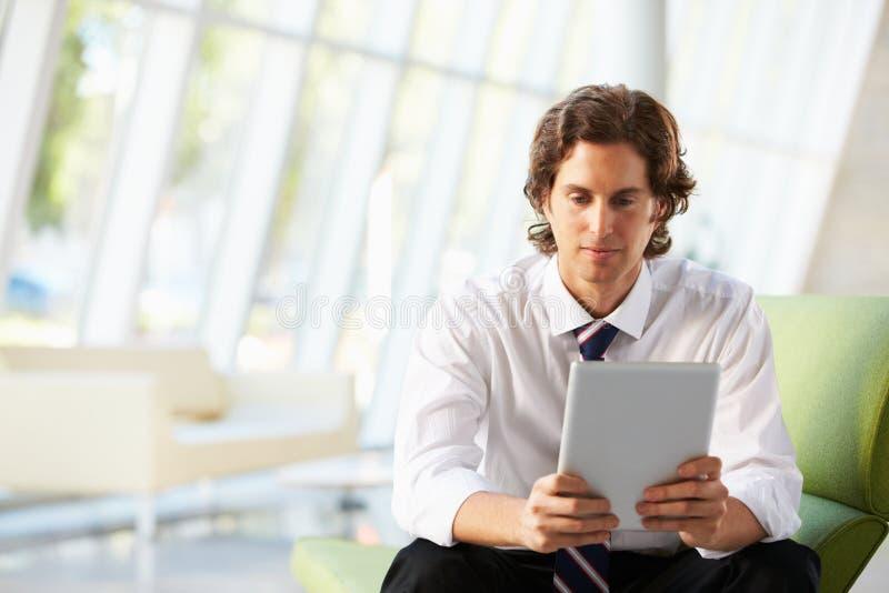 Homme d'affaires s'asseyant sur le sofa dans le bureau utilisant la tablette de Digitals photographie stock libre de droits