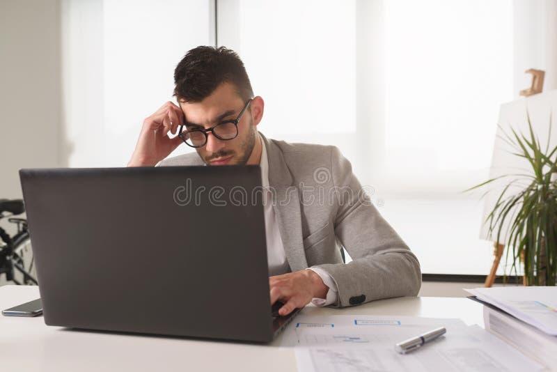 Homme d'affaires s'asseyant sur son bureau Analyse des rapports, inqui?t?s photographie stock libre de droits