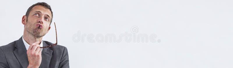 Homme d'affaires 40s boudant tenant ses lunettes pour la stratégie de inspiration, bannière photo libre de droits