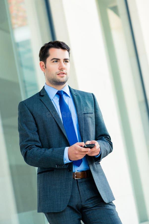 Homme d'affaires sûr extérieur utilisant le téléphone image libre de droits