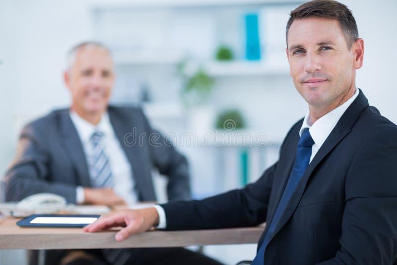Download Homme D'affaires Sûr Regardant L'appareil-photo Avec Le Collègue Derrière Photo stock - Image du heureux, présidence: 56481940