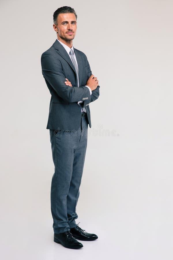 Homme d'affaires sûr se tenant avec des bras pliés image stock