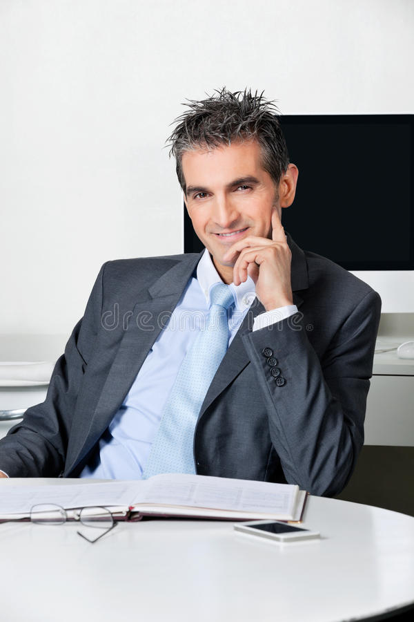 Homme d'affaires sûr Sitting At Desk image libre de droits