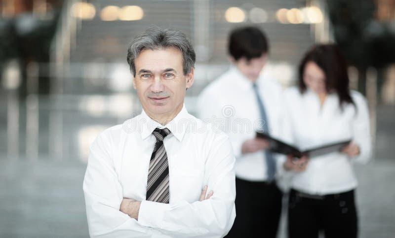 Homme d'affaires s?rieux sur le fond de l'?quipe d'affaires photographie stock