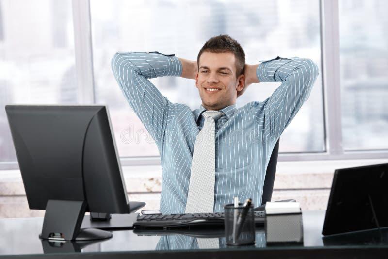 Homme d'affaires satisfaisant souriant au bureau photographie stock libre de droits