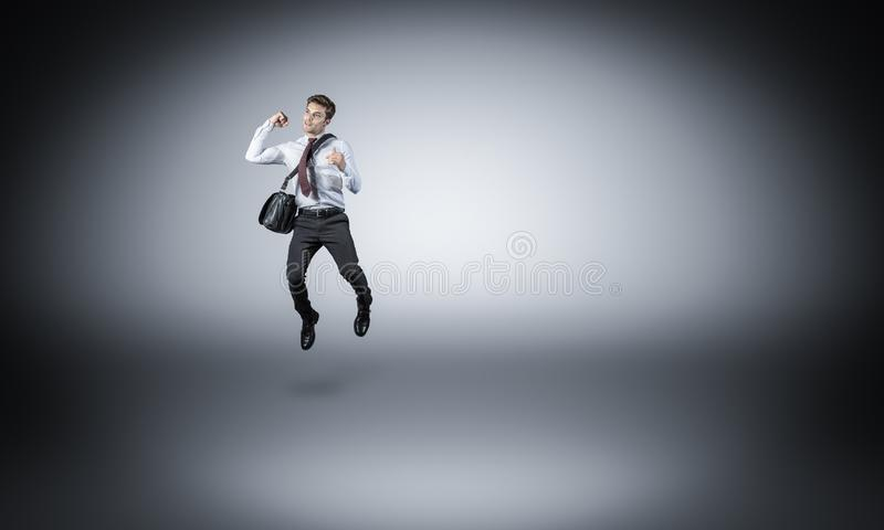 Homme d'affaires sautant sur le gris photographie stock