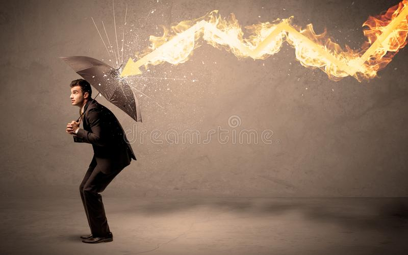 Homme d'affaires se défendant d'une flèche du feu avec un parapluie images stock