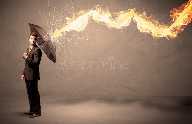 Homme d'affaires se défendant d'une flèche du feu avec un parapluie photo stock
