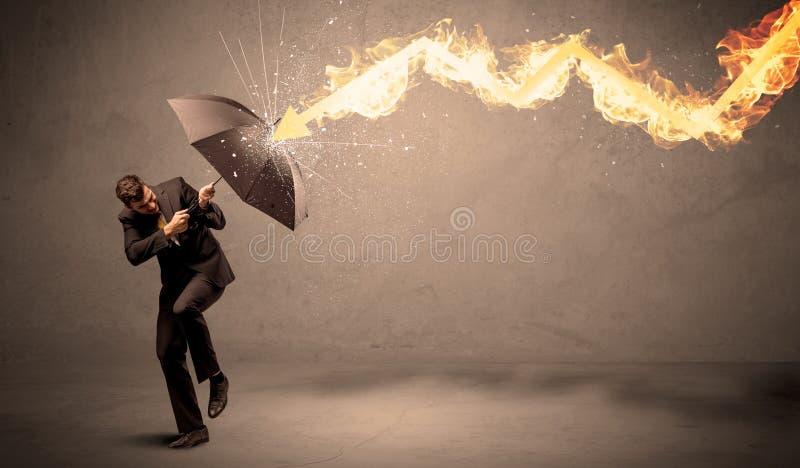 Homme d'affaires se défendant d'une flèche du feu avec un umbrell image libre de droits