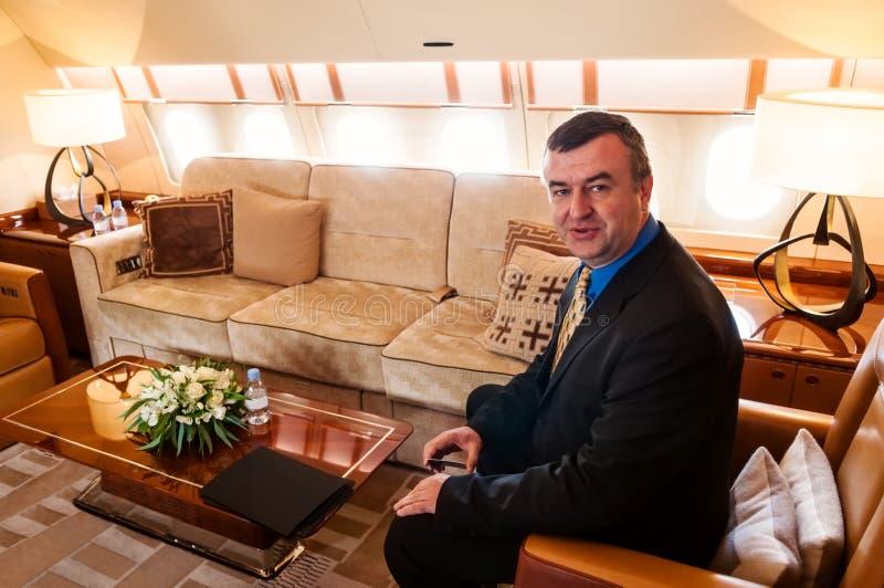 Homme d'affaires se déplaçant par l'avion à réaction commercial d'air photographie stock