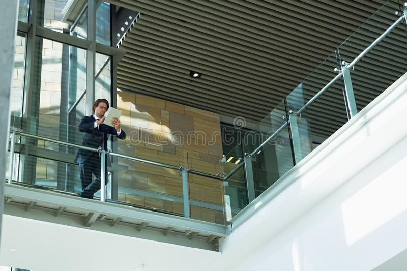 Homme d'affaires se penchant sur la balustrade et à l'aide du comprimé numérique dans le couloir au bureau moderne image stock