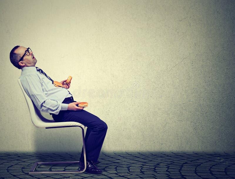 Homme d'affaires se sentant fatigué et somnolent après consommation de trop d'hamburgers pour le déjeuner photos stock