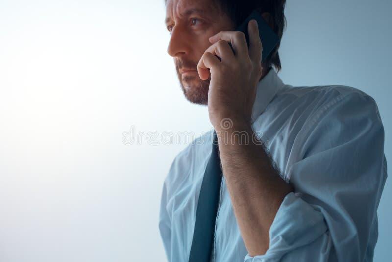 Homme d'affaires se tenant à côté de la fenêtre de bureau et parlant sur le mobile photographie stock libre de droits