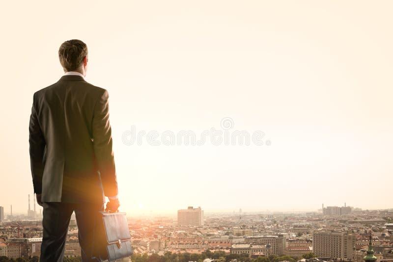 Homme d'affaires se tenant avec le dos contre la ville images stock