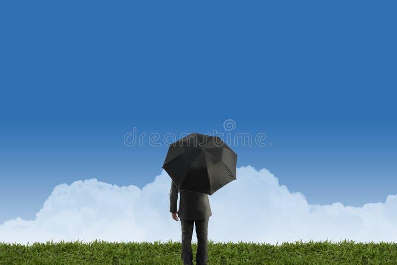 Homme d'affaires se tenant avec le parapluie sur l'herbe verte photographie stock
