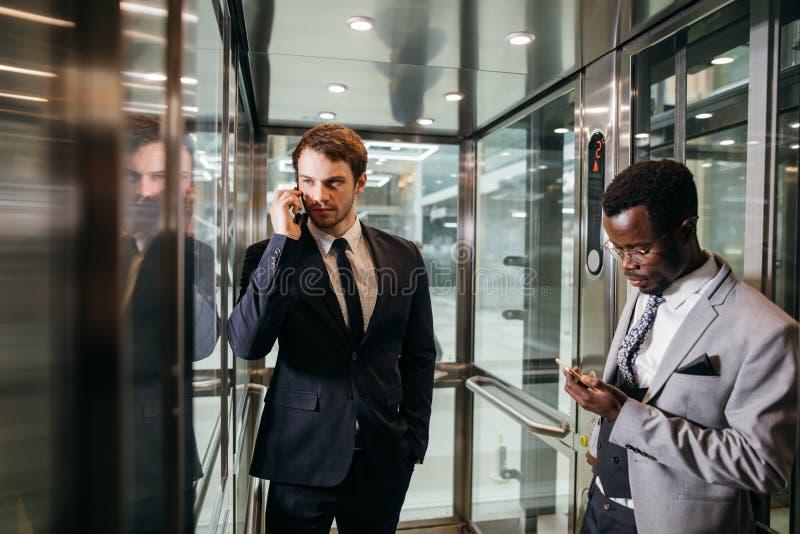 Homme d'affaires se tenant dans l'ascenseur et le smartphone d'utilisation photo libre de droits