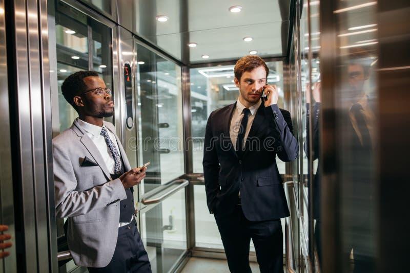 Homme d'affaires se tenant dans l'ascenseur et le smartphone d'utilisation image libre de droits