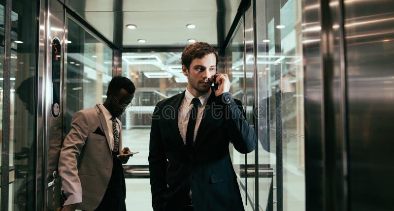Homme d'affaires se tenant dans l'ascenseur et le smartphone d'utilisation photographie stock libre de droits