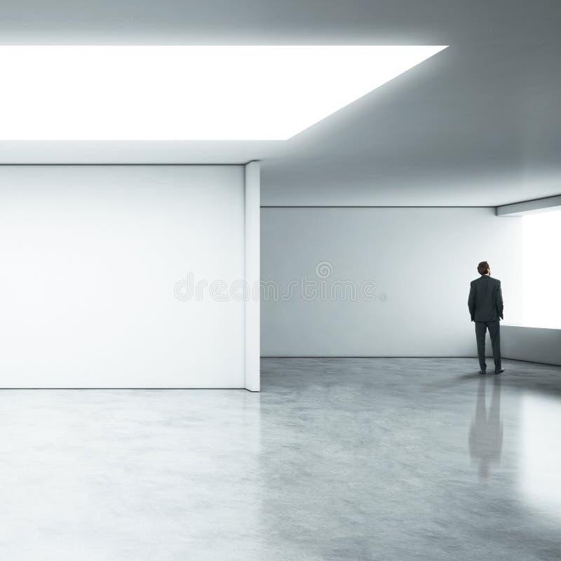 Homme d'affaires se tenant dans le bureau blanc image stock