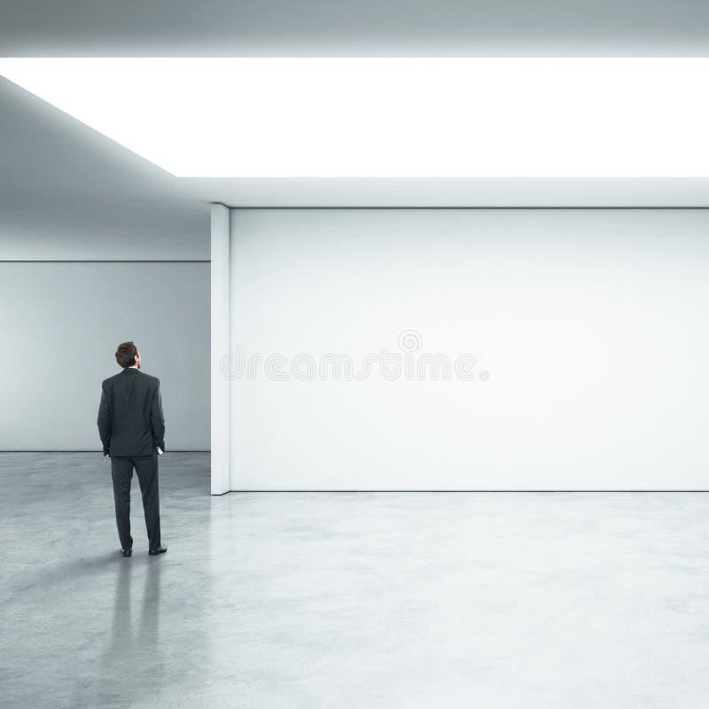 Homme d'affaires se tenant dans le bureau lumineux photographie stock libre de droits