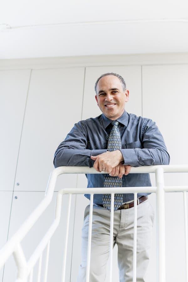 Homme d'affaires se tenant dans le sourire de couloir de bureau image libre de droits