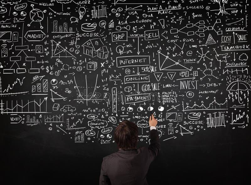 Homme d'affaires se tenant devant les diagrammes tirés sur un tableau noir photo stock